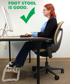 Woman working on computer at desk with foot stool, feet are flat on the stool and posture is straight